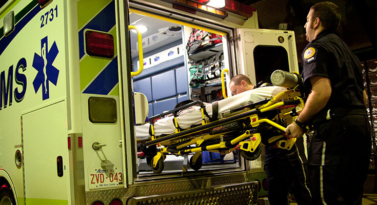 Emergency personnel loading a stretcher into ambulance