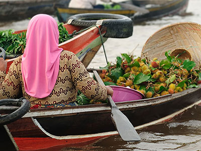 Young Indonesian girl transports goods across waterway