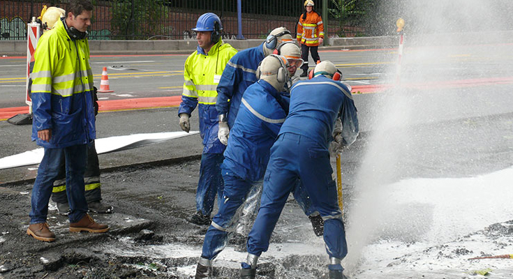 Workers repair a pipeline under a section of pavement