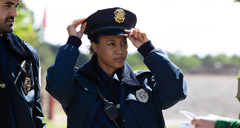 A police woman adjust her hat as she approaches a crash scene