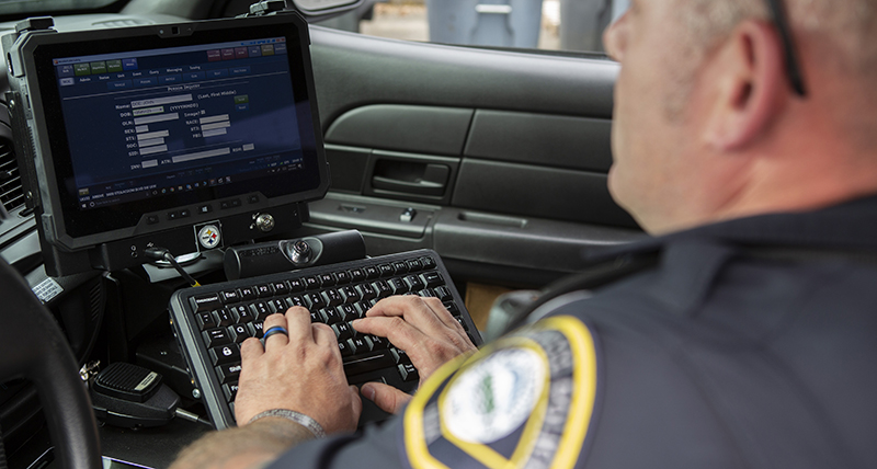 A male police officer enters data via his car computer