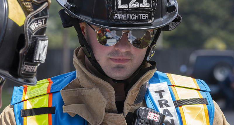 Male firefighter looks down a a tablet in his hands at an accident scene