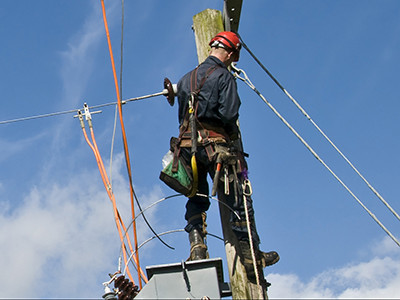 A maintenance worker fixes power lines using G/Technology